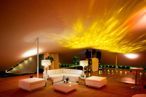 50th birthday party in stretch tent with white contemporary furniture and amber lighting