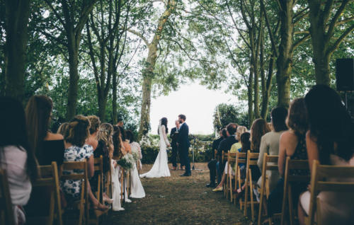 Outdoor ceremony beneath a canopy of trees