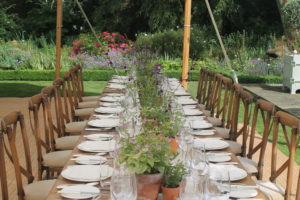 Long naked rustic tables, crossback chairs and fresh potted herbs
