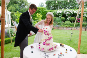 Cutting the cake, decorated with orchids