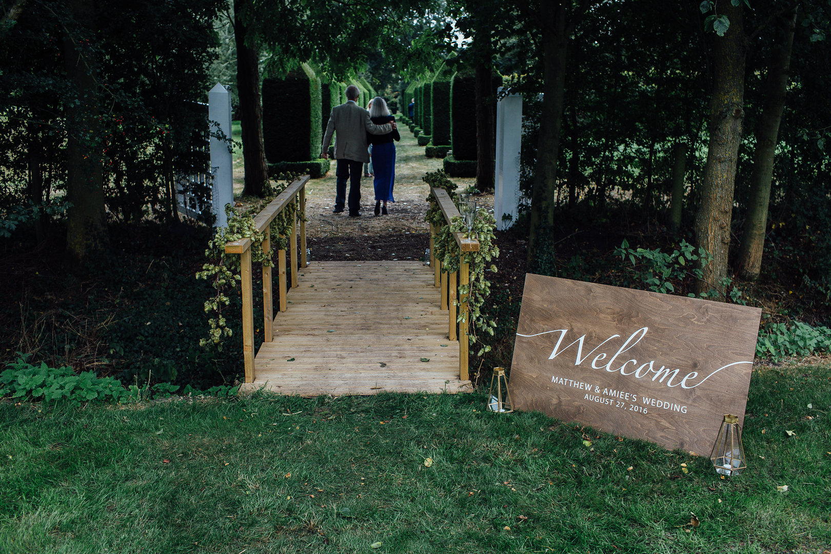 Wedding entrance over the moat and along a walkway of obelisk topiary.
